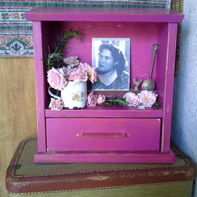 a small magenta personal altar, called a zendohous, in honor of a family ancestor, with photo, flowers and other memorabilia