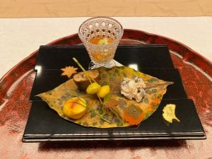 an elegant lunch presentation features a fried ginkgo leaf in fall yellow, ginkgo nuts speared with pine needles, and mushrooms, garnished artfully with dried leaves and served on a giant leaf.