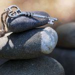 a decorative metal key sits on tumbled stones