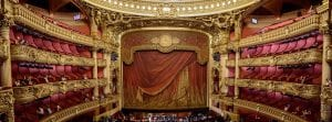 this shows a beautiful and elaborate theater with a heavy red curtain decorated with gold and 4 levels of box seats