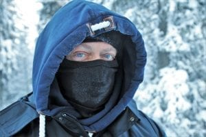 man in snowy weather with mask covering his nose and mouth
