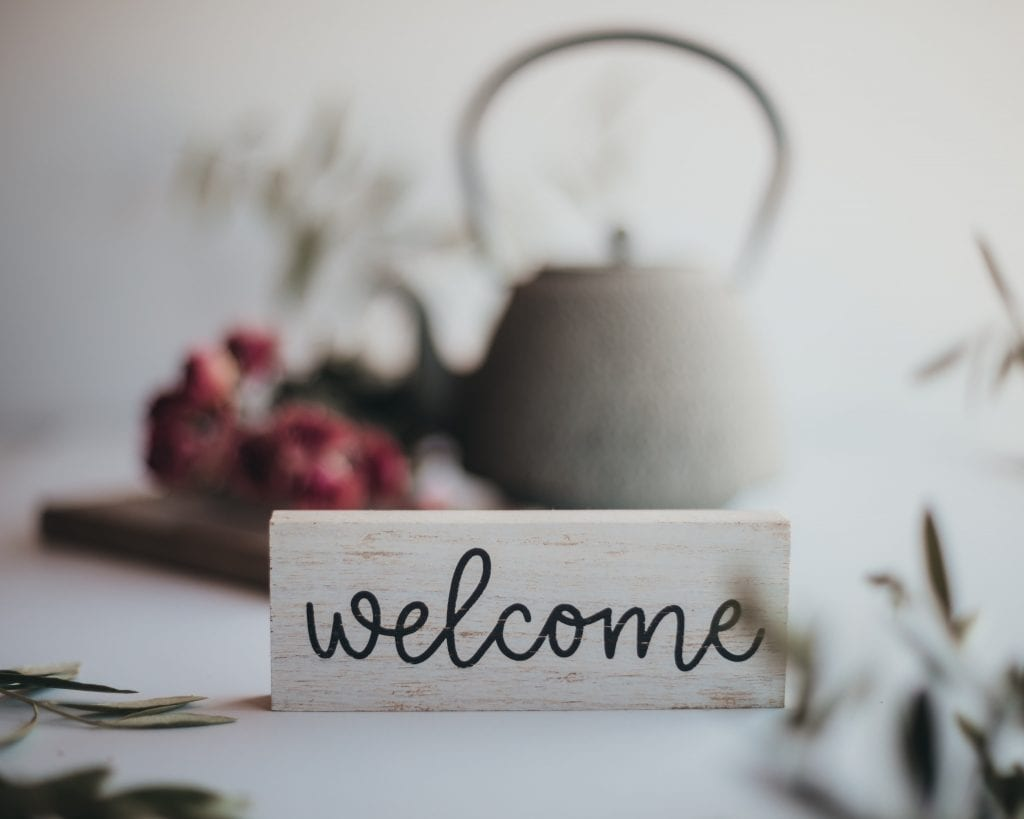 "a friendly ""welcome"" sign, along with flowers and a tea pot"