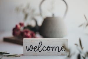 """a friendly """"welcome"""" sign, along with flowers and a tea pot"""