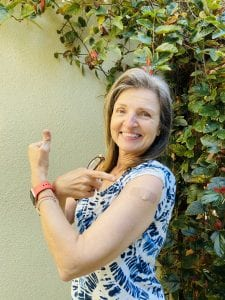 woman showing her bandaid where the Moderna vaccine was administered