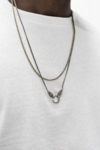 gold and silver jewelry adorns a man's white tee